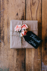 Rustic gift with slate tag with the word 'thank you' written on it