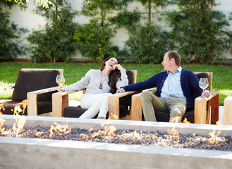 Couple relaxing at outdoor lounge fire pit with wine
