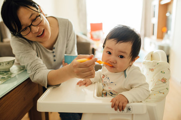 Chinese young mother feeding her littler baby boy