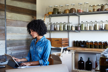 Millennial African American Woman businesswoman on computer in her skincare studio