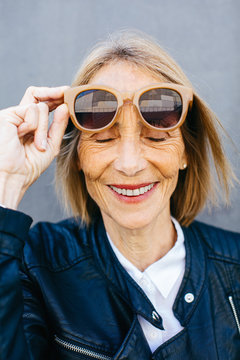 Smiling senior woman holding sunglasses