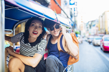 Couple Riding in a Tuk Tuk Taxi in Bangkok