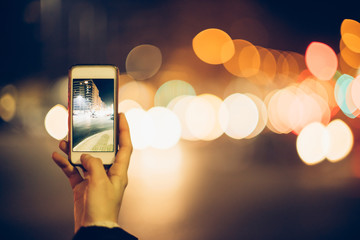 taking photo with a smartphone on street at night