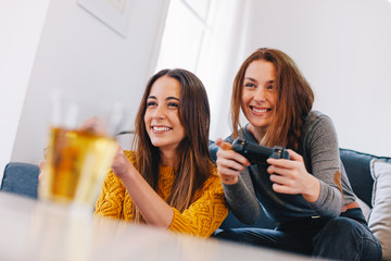Two happy young female playing video games at home