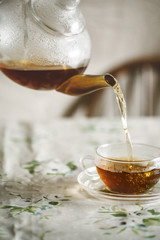 Morning tea being poured from a glass teapot into a glass cup