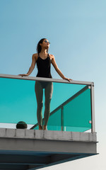 Attractive young female in black tricot standing on balcony and looking to sun