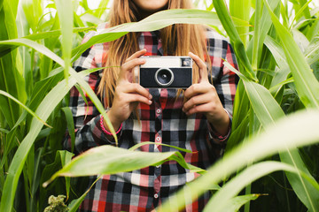 Anonymous teen girl holding an old camera in a corn field