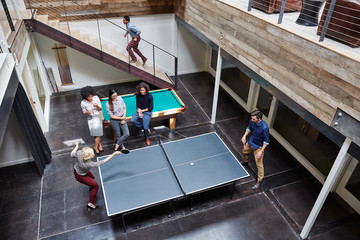 Group portrait of millennials playing ping pong at work