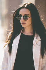 portrait of trendy woman with round sunglasses on the street