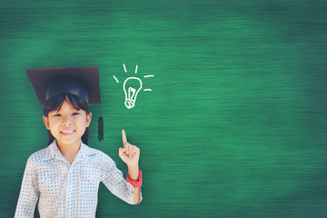 Asian Young girl has a bright idea as she stands against the blackboard at school