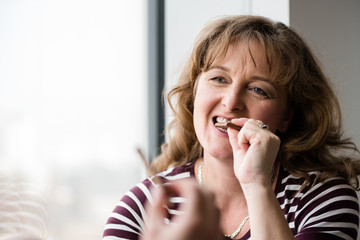 Mature smiling woman biting chocolate bar