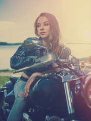 Young girl sitting on a motorcycle. Sunset.