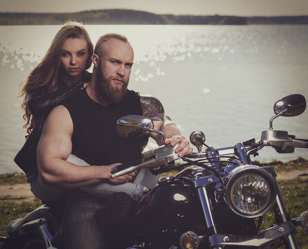 Two people and bike - young woman and bearded man on the motorbike. Adventure and vacations concept. VIntage toned image.
