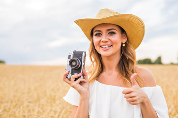 Pretty girl with vintage camera outdoors