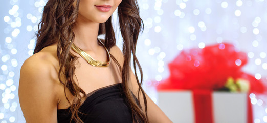Young beautiful slim curly brunette girl in black small dress with open shoulders in the room with garland in blur on background