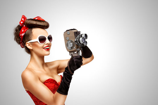 Retro movie style / Retro photo of a pin-up girl with an old vintage 8 mm camera on grey background.