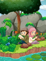 Two muslim kids reading by the river
