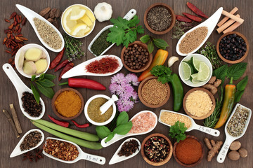 Large spice and herb selection high in antioxidants and vitamins on oak background.