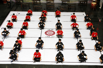 People sit on the chessboard of traditional chess game that is listed as a local intangible cultural heritage during China's first Culture and Nature Heritage Day in Mengcheng
