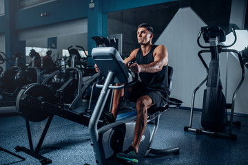 Muscular athlete training legs on exercise machine