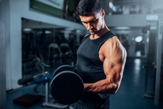 Tanned muscular athlete workout with dumbbell