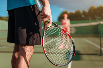 Male and female person playing tennis outdoor