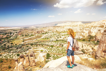 A young woman traveler stands on a mountain and admires the view. Turkey, Cappadocia