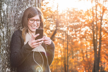 Young laughing woman, listening Music on her Smartphone in Autumn Park