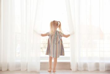 Cute little girl standing near windowsill