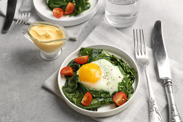 Delicious eggs Florentine with tomatoes on kitchen table