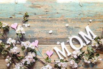 Mothers day message with apple blossom on old wooden background. Copy space. Top view.