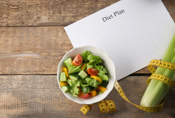 Diet plan, healthy foods and measuring tape on wooden background