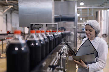 Young happy female worker in bottling factory writing notes about bottles before shipment. Inspection quality control.