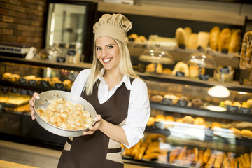 Woman who works in a bakery posing with a casserole in which the pastry