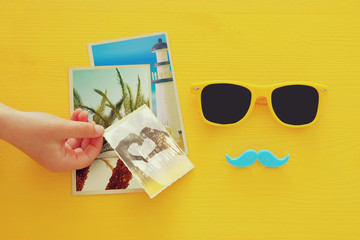 Father's day concept. Hipster yellow sunglasses and funny moustache next to photographs