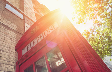 Red Telephone Booth with sun at summer in London street