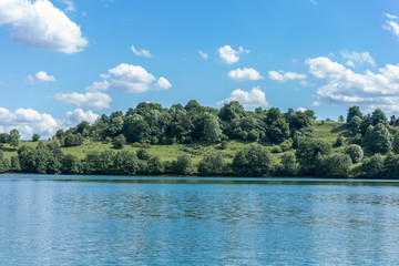 Close on a lake side mount with trees and forest on the Maar vulcan lake - blue cloudy sky landscape