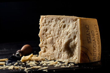 Slice of parmesan cheese with black background