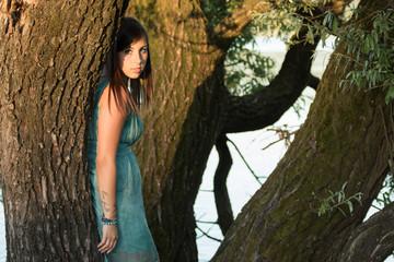 Giovane donna in abito elegante tra gli alberi sul lago