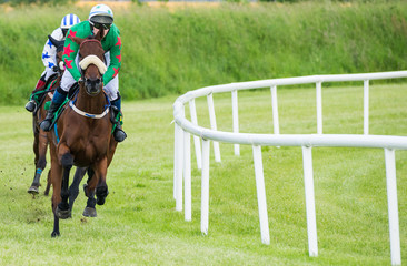 Jockey and race horse in first position taking the final turn towards the finish line