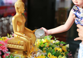 Water blessing ceremony for Songkran Festival or Thai New Year. Child girl paying respects to a statue of Buddha by pouring water onto it.