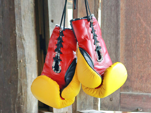 Pair of red-yellow boxing gloves Hanging on wooden.