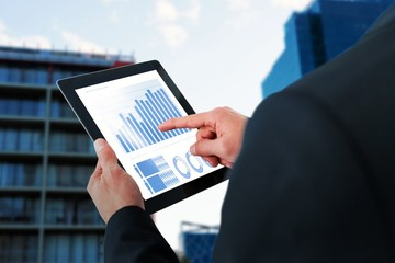 Composite image of businessman touching digital tablet