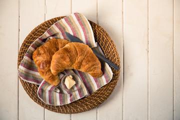 Fresh croissants in wicker basket