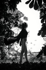 A sexy girl or female sex, in a sexy body suit and flying raincoat, stands confidently in sunglasses, between the leaves of two chestnut trees. Monochrome photo