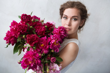 beautiful girl with pink peonies bouquet at wall. The bride with a bouquet.