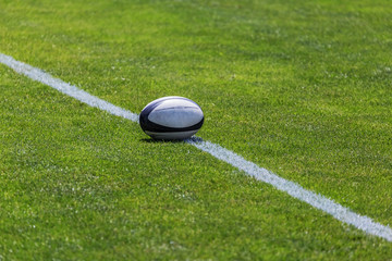 Rugby ball on green pitch and white line