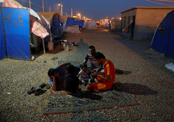 Evacuees rest outside their tent inside a refugee camp for people who fled from Mosul due to fighting between Iraqi forces and Islamic State militants, in the outskirts of Erbil