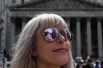"""The U.S. flag is reflected in a woman's sunglasses during an event called """"March Against Sharia"""" in New York City"""