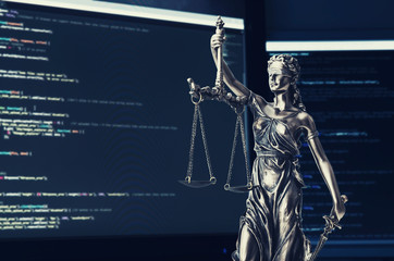 Justice statue with code on screen in background